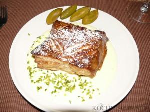 Blätterteigtasche mit Pflaumen-Pistazien-Füllung auf frischer Vanillesauce